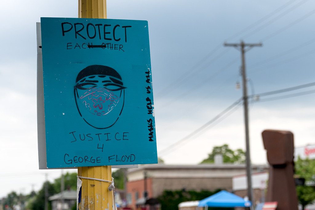 "A sign that says ""protect each other; justice for George Floyd"""