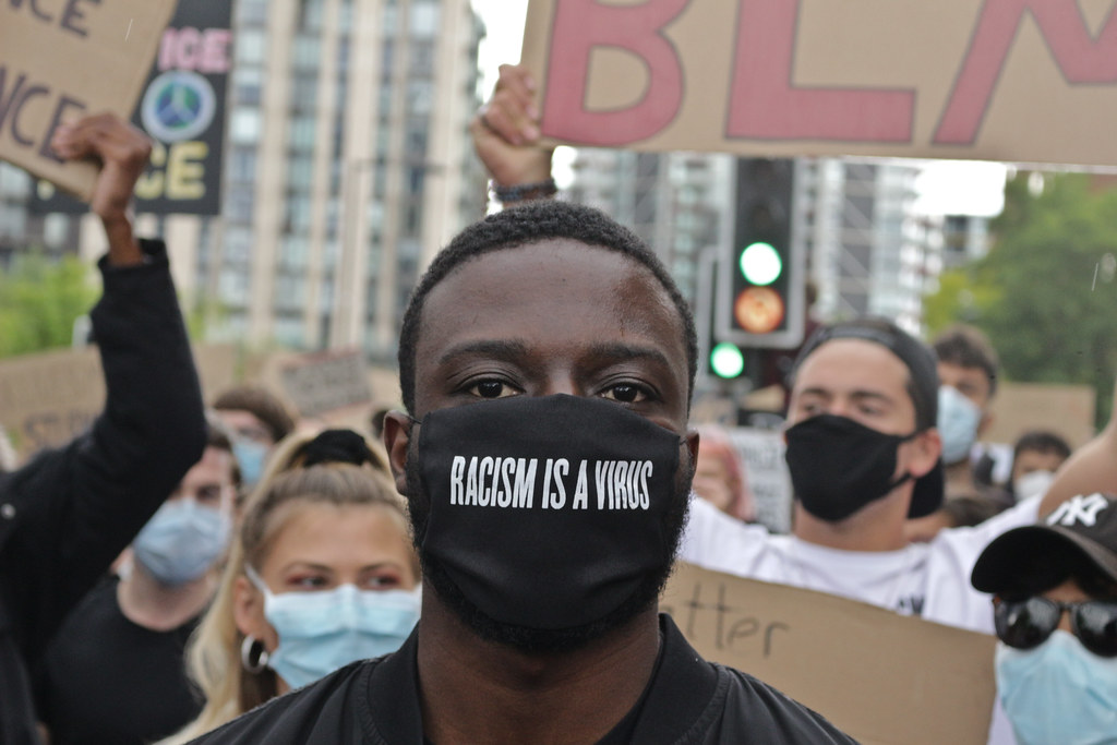 "Man in a ""Racism is a Virus"" mask"